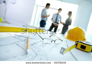 stock-photo-image-of-engineering-objects-on-workplace-with-three-partners-interacting-on-background-93376240
