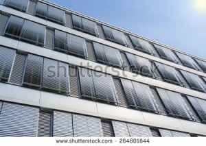 stock-photo-facade-of-modern-high-rise-office-building-with-covered-windows-venetian-blinds-against-blue-sky-264801644