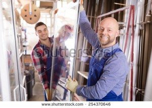 stock-photo-portrait-of-two-workers-in-coverall-working-with-pvc-window-at-factory-254370646